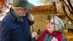 An elderly couple look at each other.