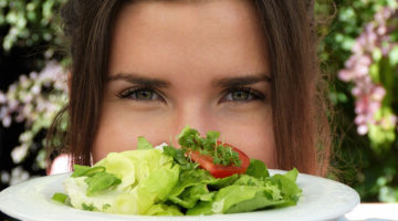 A lady holding up a plate of salad.
